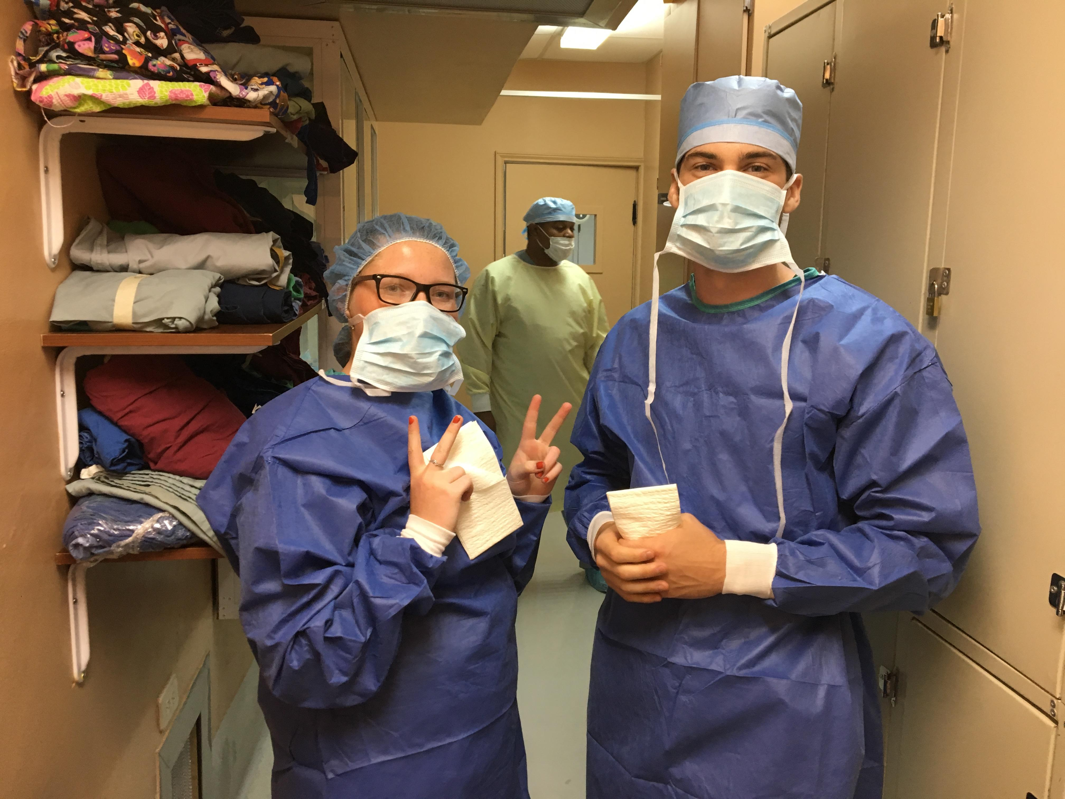 Two Projects Abroad interns are pictured getting ready to go to an operating room and watch over local doctors whilst on their Public Health internship in Belize.